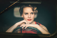 Woman in retro car. Beautiful woman in a red dress is sitting at the wheel of an old car. Through the glass Stock Images