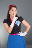 Woman in retro clothes with finger on lips Stock Image