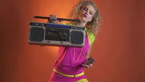 Woman in retro clothes puts the boombox on her shoulder. Young blonde woman in pink and green retro clothes, with colorful make up, with a cassette in her hand stock video footage