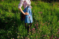Woman in retro clothing standing amongst flowers. Young woman enjoying sunny day in a meadow Stock Image