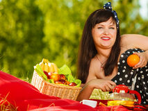 Woman in retro dress having picnic on meadow. Summertime relaxation and recreation concept. Woman in retro dress having picnic on meadow, having basket with Royalty Free Stock Image