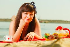 Woman in retro dress having picnic near sea. Summertime relaxation and recreation concept. Woman in retro dress having picnic near sea, having basket with fruits Royalty Free Stock Image