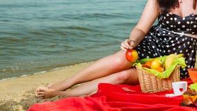 Woman in retro dress having picnic near sea Stock Images