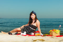 Woman in retro dress having picnic near sea. Summertime relaxation and recreation concept. Woman in retro dress having picnic near sea, having basket with fruits Royalty Free Stock Images