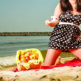 Woman in retro dress having picnic near sea. Summertime relaxation and recreation concept. Woman in retro dress having picnic near sea, having basket with fruits Royalty Free Stock Photography