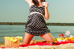 Woman in retro dress having picnic near sea. Summertime relaxation and recreation concept. Woman in retro dress having picnic near sea, having basket with fruits Stock Photos
