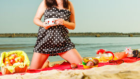 Woman in retro dress having picnic near sea. Summertime relaxation and recreation concept. Woman in retro dress having picnic near sea, having basket with fruits Royalty Free Stock Photo