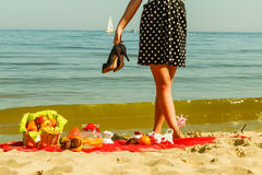 Woman in retro dress having picnic near sea. Summertime relaxation and recreation concept. Woman in retro dress having picnic near sea, having basket with fruits Royalty Free Stock Photos