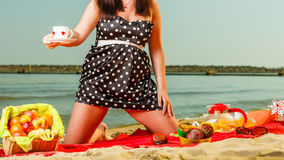 Woman in retro dress having picnic near sea. Summertime relaxation and recreation concept. Woman in retro dress having picnic near sea, having basket with fruits Stock Image