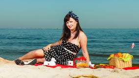 Woman in retro dress having picnic near sea. Summertime relaxation and recreation concept. Woman in retro dress having picnic near sea, having basket with fruits Stock Photography