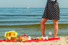 Woman in retro dress having picnic near sea. Summertime relaxation and recreation concept. Woman in retro dress having picnic near sea, having basket with fruits Stock Images
