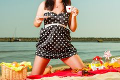 Woman in retro dress having picnic near sea. Summertime relaxation and recreation concept. Woman in retro dress having picnic near sea, having basket with fruits Stock Photo