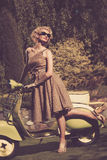 Woman with moped outdoors Stock Images