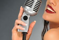 Woman with a retro microphone. Picture of a Woman with a retro microphone royalty free stock photography