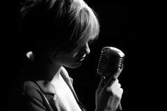 Woman with retro microphone. Singing woman with retro microphone royalty free stock photo