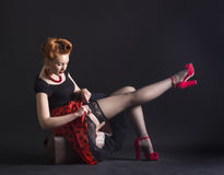 Woman in retro style flirtatiously straightens stockings Stock Photos