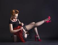 Woman in retro style flirtatiously straightens stockings Stock Photos