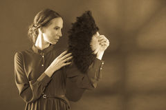 Woman retro style holds feather fan, sepia tone Royalty Free Stock Photos