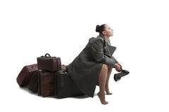 Woman with retro suitcases. Beautiful young woman with retro style suitcases in military greatcoat Stock Photography