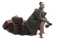 Woman with retro suitcases. Beautiful young woman with retro style suitcases in military greatcoat Royalty Free Stock Photos