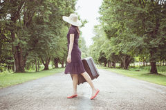 Woman with retro vintage luggage on empty street Stock Image