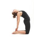 Woman in reversed yoga posture. Young attractive woman in back reversed yoga pose, side view, dressed in black on white background Royalty Free Stock Photos