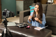 Woman reviewing beauty products online. Portrait of an attractive young woman talking about some beauty products for her video blog at home royalty free stock photo