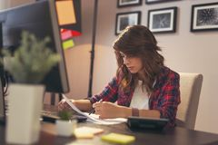 Woman reviewing documents in a home office. Young woman reviewing documents, working late in a home office stock images