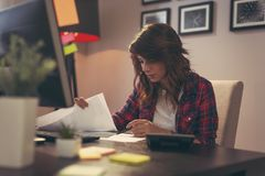 Woman reviewing documents in home office. Young woman reviewing documents, working late in a home office royalty free stock photography