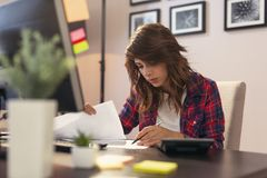 Woman reviewing documents in a home office royalty free stock image