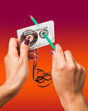 Woman rewind a cassette tape with a pencil. Woman rewind a retro cassette with loose tape using a pencil royalty free stock image