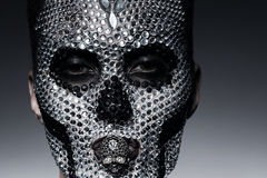Woman in rhinestones with skull face. In studio Stock Photography