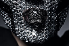 Woman in rhinestones with skull in mouth. In dark Royalty Free Stock Photography