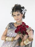 Woman in rich sari holding roses Stock Photo
