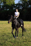 Woman ride back horse in a evening field Stock Photography
