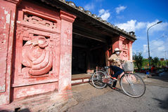 Woman ride bicycle at Japanese bridge, Hoi An Stock Photography