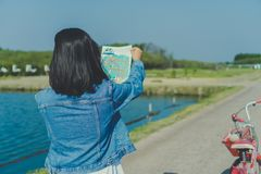 Woman ride bicycle in small road to nature while look at travel map royalty free stock photography