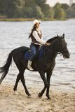 Woman ride the horse. Near water Stock Photo