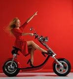 Woman ride new electric car motorcycle bicycle scooter with hands pointing finger up freedom sign laughing smiling. On red background surprised stock images