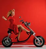 Woman ride new electric car motorcycle bicycle scooter with hands spread freedom sign laughing smiling on red background royalty free stock image