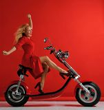 Woman ride new electric car motorcycle bicycle scooter with hands spread freedom sign laughing smiling on red background. Surprised stock image