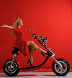 Woman ride new electric car motorcycle bicycle scooter with hands spread freedom sign laughing smiling on red background. Surprised royalty free stock photography