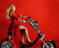 Woman ride new electric car motorcycle bicycle scooter present for new year 2019 in red dress on red background surprised. Woman ride new electric car motorcycle stock images