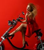Woman ride new electric car motorcycle bicycle scooter present for new year 2019 in red dress on red background. Looking at the corner royalty free stock photography