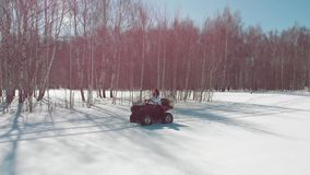 Woman ride a quad bike in the snow field on the background of a birch forest. Shot from drone stock video footage