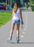 Woman ride rollerblades in the park. Back view. Stock Photos