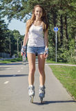 Woman ride rollerblades in the park. Stock Images