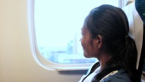 Woman ride in shinkansen and turns to the camera. Portrait of a girl watching the landscape from a window of a moving express train. Passenger in fast train stock video
