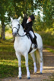 Woman  ride on white horse in wood Stock Photos