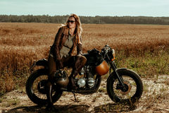 Woman rider with his vintage custom made cafe racer Royalty Free Stock Images